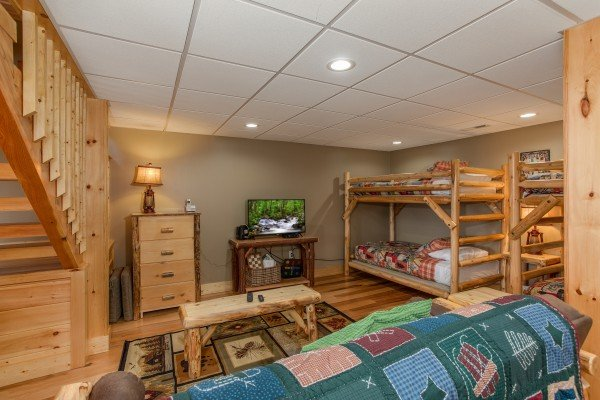 Futon, TV, and bunk beds on the lower floor at Moonlight Inn Gatlinburg, a 2 bedroom cabin rental located in Gatlinburg