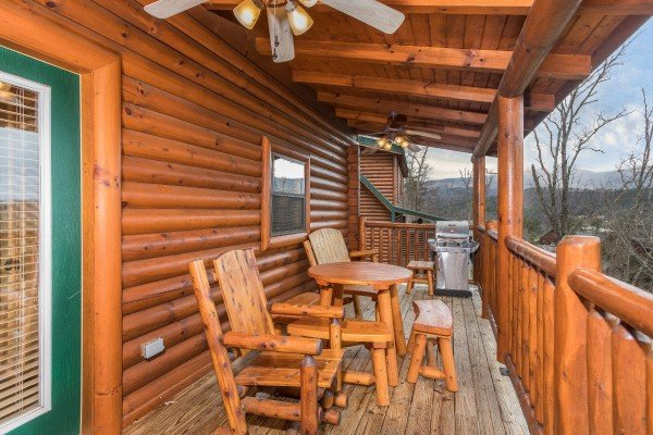 Dining table for two and a propane grill on a covered deck at Heaven on Earth, a 2-bedroom cabin rental located in Pigeon Forge