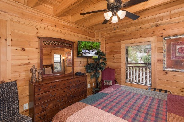 Bedroom with a dresser and mirror and a TV at Heaven on Earth, a 2-bedroom cabin rental located in Pigeon Forge