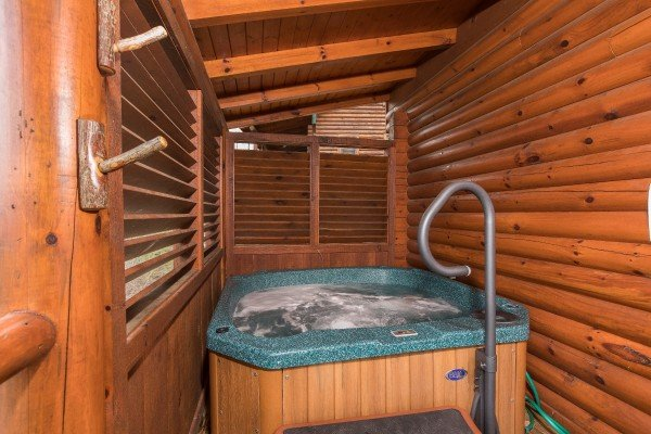 Hot tub with privacy fence on the covered deck at Heaven on Earth, a 2-bedroom cabin rental located in Pigeon Forge