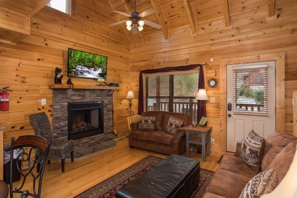 Living room with a fireplace, tv, and vaulted ceiling at Heaven on Earth, a 2-bedroom cabin rental located in Pigeon Forge