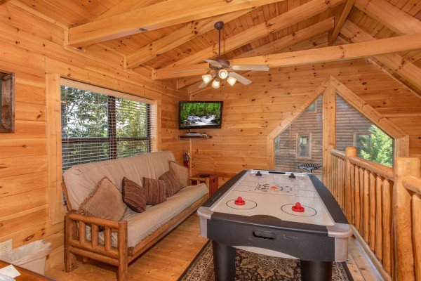 Loft with a futon and air hockey table at Heaven on Earth, a 2-bedroom cabin rental located in Pigeon Forge