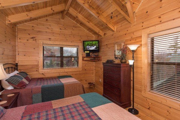 Bedroom with two queen beds, a TV, and a chest of drawers at Heaven on Earth, a 2-bedroom cabin rental located in Pigeon Forge
