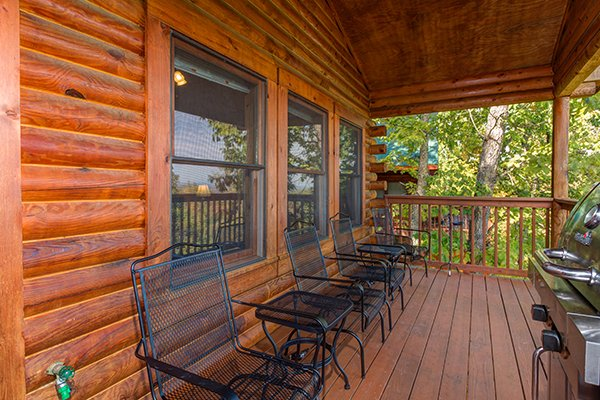 Seating and a grill on the covered deck at Lookout Ridge, a 2 bedroom cabin rental located in Pigeon Forge