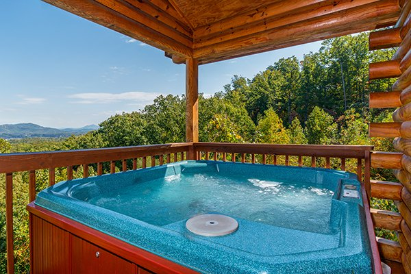 The wooded side view of the hot tub at Lookout Ridge, a 2 bedroom cabin rental located in Pigeon Forge