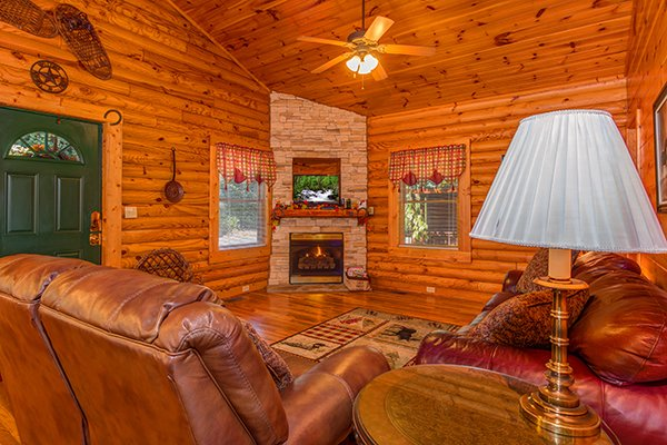 Corner stone fireplace with a tv at Lookout Ridge, a 2 bedroom cabin rental located in Pigeon Forge