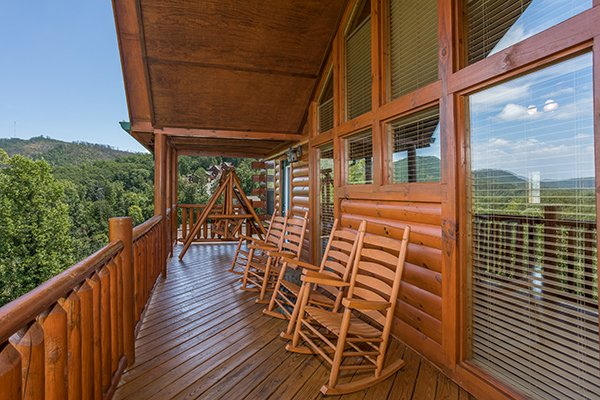 Covered deck with rocking chairs at Shangri-lodge, an 8 bedroom cabin rental located in Pigeon Forge