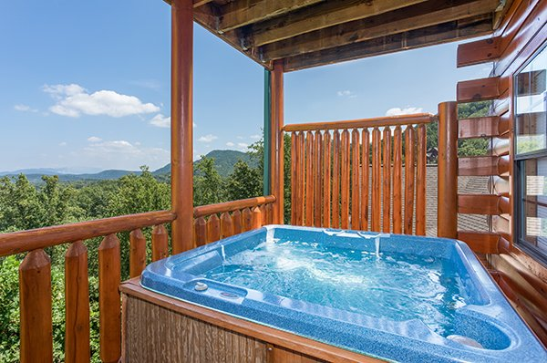 Hot tub on a deck with a privacy fence at Shangri-lodge, an 8 bedroom cabin rental located in Pigeon Forge