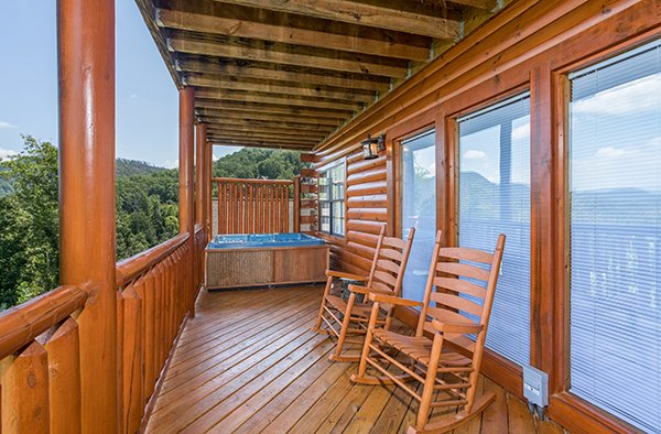 Rocking chairs and hot tub on a deck at Shangri-lodge, an 8 bedroom cabin rental located in Pigeon Forge