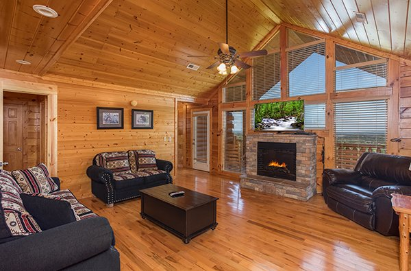 Living room with fireplace and TV at Shangri-lodge, an 8 bedroom cabin rental located in Pigeon Forge
