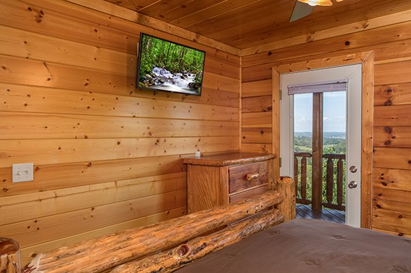 Bedroom with a dresser, TV, and deck access at Shangri-lodge, an 8 bedroom cabin rental located in Pigeon Forge
