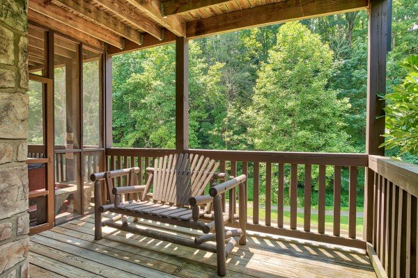 Adirondack bench on a covered porch at Mountain Music, a 5 bedroom cabin rental located in Pigeon Forge