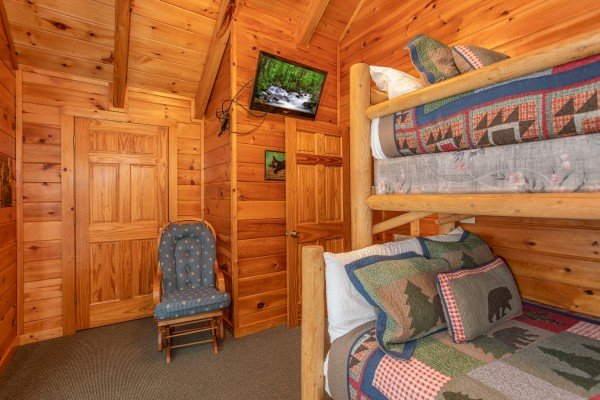Rocking chair and TV in the bunk room at Mountain Music, a 5 bedroom cabin rental located in Pigeon Forge