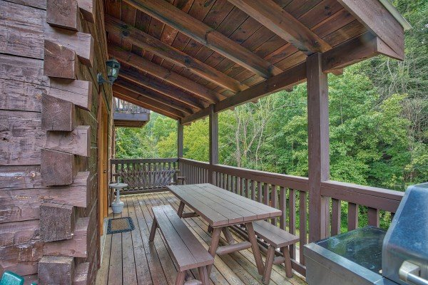 Picnic table on a covered deck at Mountain Music, a 5 bedroom cabin rental located in Pigeon Forge