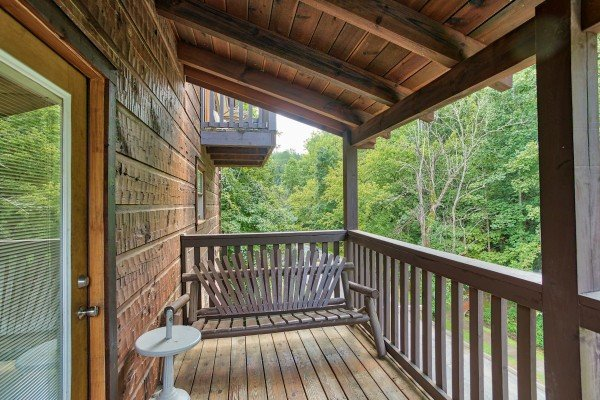 Bench on a covered deck at Mountain Music, a 5 bedroom cabin rental located in Pigeon Forge