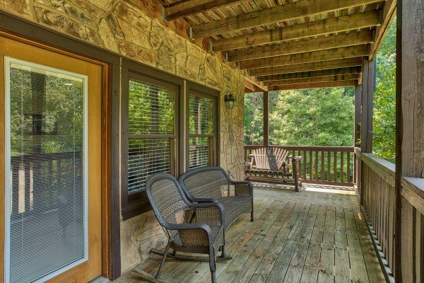 Rocker and benches on the covered porch at Mountain Music, a 5 bedroom cabin rental located in Pigeon Forge
