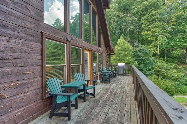 Adirondack chairs and a grill on the deck at Mountain Music, a 5 bedroom cabin rental located in Pigeon Forge