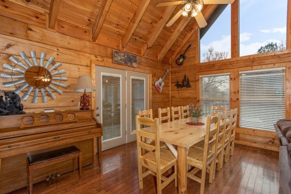 Piano and dining table for ten at Mountain Music, a 5 bedroom cabin rental located in Pigeon Forge