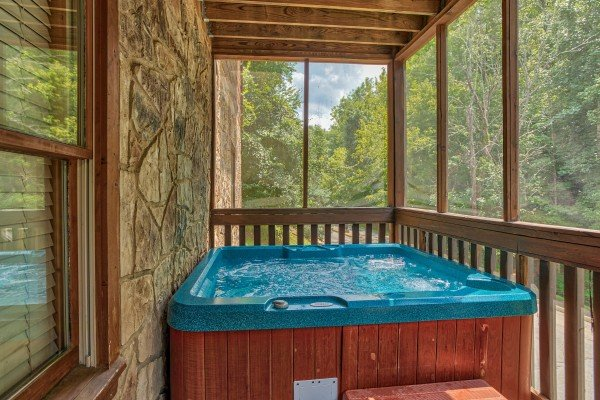 Hot tub on a screened and covered porch at Mountain Music, a 5 bedroom cabin rental located in Pigeon Forge