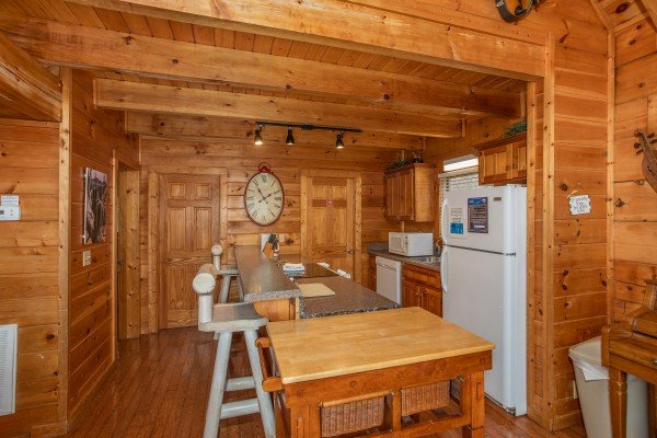 Kitchen with white appliances and breakfast bar at Mountain Music, a 5 bedroom cabin rental located in Pigeon Forge