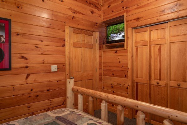 TV and closet in a bedroom at Mountain Music, a 5 bedroom cabin rental located in Pigeon Forge