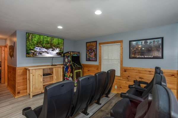 TV and arcade game in the theater room at Mountain Music, a 5 bedroom cabin rental located in Pigeon Forge