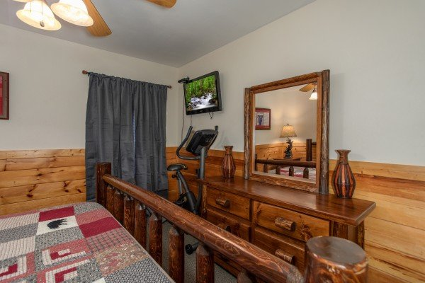 Dresser, exercise bike, and TV in a bedroom at Mountain Music, a 5 bedroom cabin rental located in Pigeon Forge