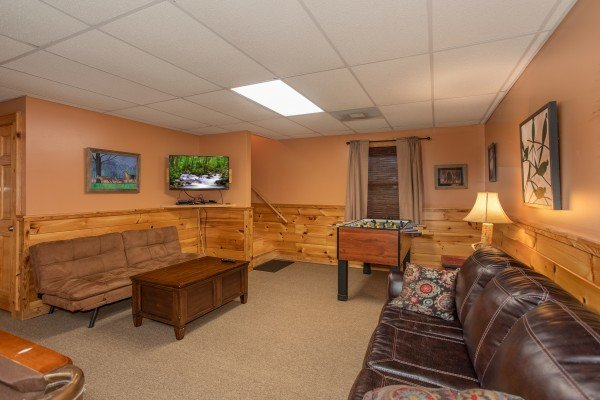 Game room with TV, foosball, and sofas at Granny D's, a 2 bedroom cabin rental located in Pigeon Forge