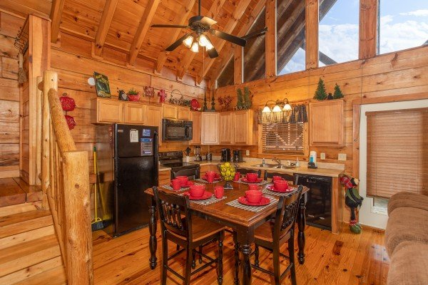 Dining space for six in the kitchen with black appliances at Granny D's, a 2 bedroom cabin rental located in Pigeon Forge