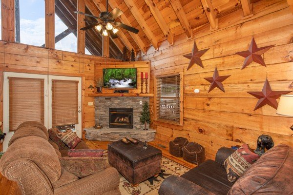 Living room with vaulted ceiling, fireplace, TV, and deck access at Granny D's, a 2 bedroom cabin rental located in Pigeon Forge