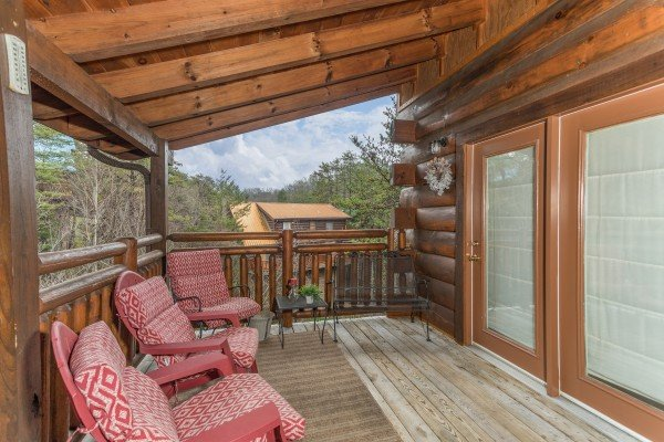 Seating on the covered deck at Granny D's, a 2 bedroom cabin rental located in Pigeon Forge