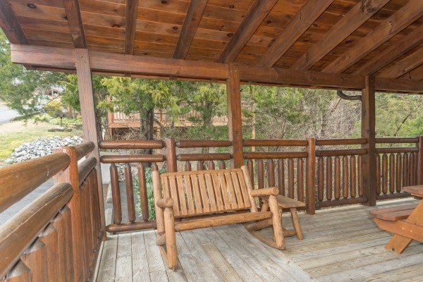 Rocking bench on the covered deck at Granny D's, a 2 bedroom cabin rental located in Pigeon Forge