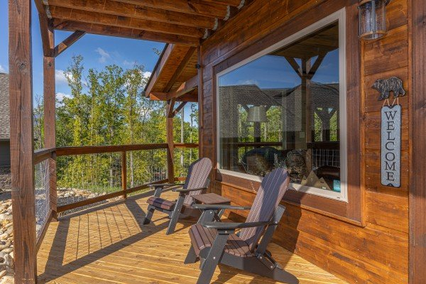 Adirondack chairs on a covered deck at Heaven's Hill, a 3 bedroom cabin rental located in Gatlinburg