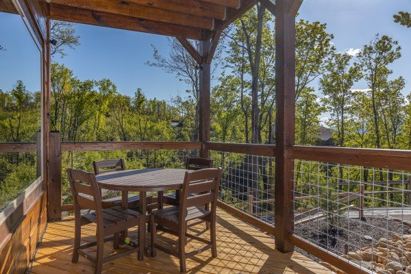 Covered deck with dining table for four at Heaven's Hill, a 3 bedroom cabin rental located in Gatlinburg
