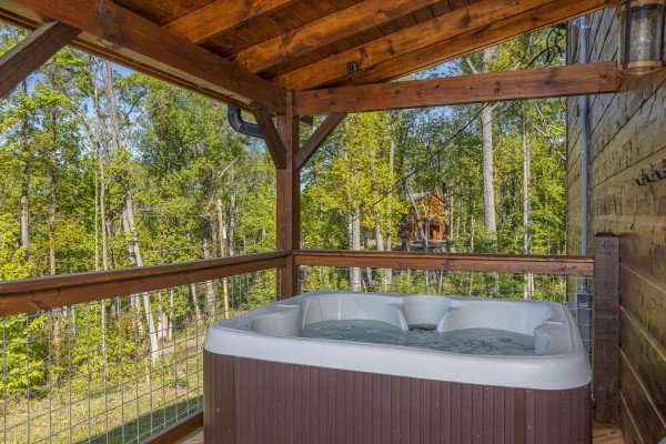 Hot tub on a covered deck at Heaven's Hill, a 3 bedroom cabin rental located in Gatlinburg