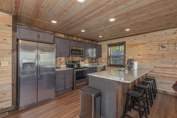 Kitchen with stainless steel appliances and breakfast bar at Heaven's Hill, a 3 bedroom cabin rental located in Gatlinburg