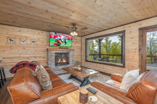 Fireplace, TV, and seating in the living room at Heaven's Hill, a 3 bedroom cabin rental located in Gatlinburg