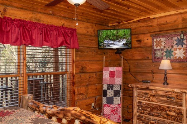 Bedroom with a dresser and TV at Moonshiner's Ridge, a 1-bedroom cabin rental located in Pigeon Forge