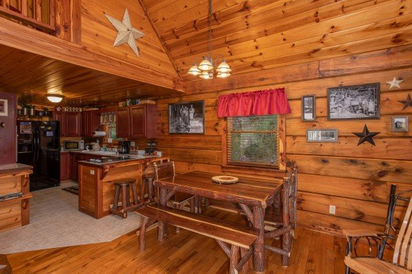 Dining room with benches and two chairs at Moonshiner's Ridge, a 1-bedroom cabin rental located in Pigeon Forge