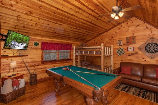 Loft space with a pool table, TV, and bunk bed at Moonshiner's Ridge, a 1-bedroom cabin rental located in Pigeon Forge