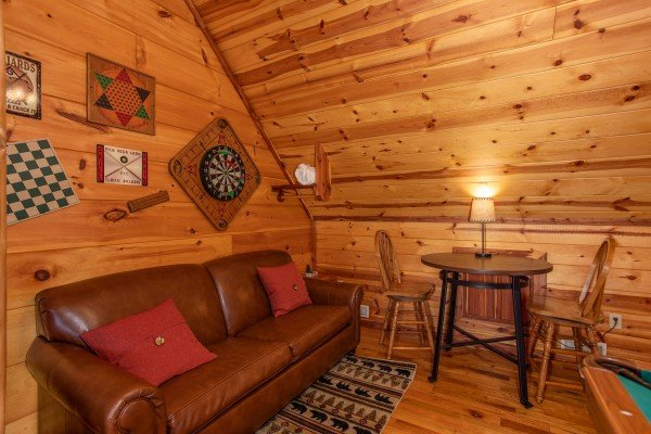Dart board and sleeper sofa in the game room at Moonshiner's Ridge, a 1-bedroom cabin rental located in Pigeon Forge