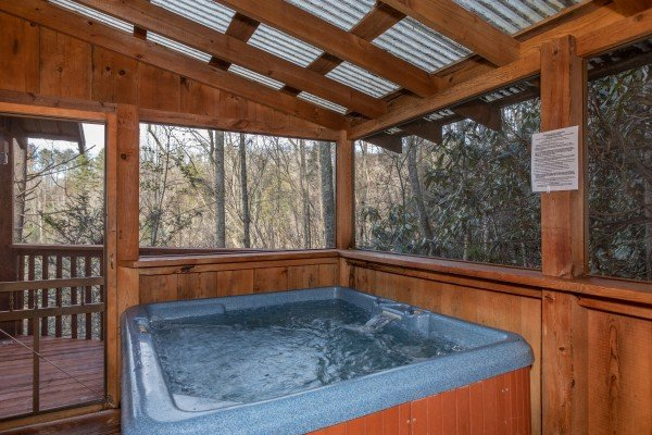 Hot tub on a covered, screened-in porch at Moonshiner's Ridge, a 1-bedroom cabin rental located in Pigeon Forge