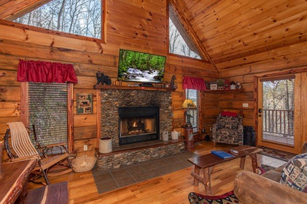 Living room with a stone fireplace, TV, and large windows near the vaulted ceiling at Moonshiner's Ridge, a 1-bedroom cabin rental located in Pigeon Forge