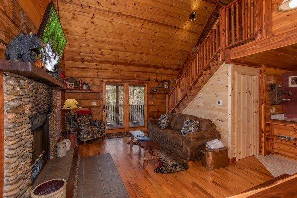 Looking from the dining space into the living room and deck at Moonshiner's Ridge, a 1-bedroom cabin rental located in Pigeon Forge
