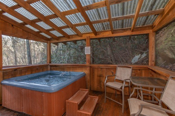 Screened in porch with a hot tub and bistro seating at Moonshiner's Ridge, a 1-bedroom cabin rental located in Pigeon Forge