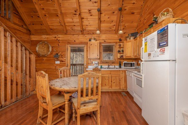 Kitchen with dining table for three and white appliances at Smoky Bears Creek, a 2 bedroom cabin rental located in Pigeon Forge