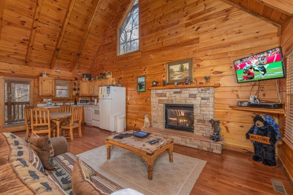Living room with fireplace and TV at Smoky Bears Creek, a 2 bedroom cabin rental located in Pigeon Forge