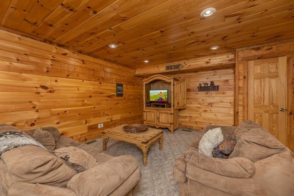 Lower living room with seating and a TV at Smoky Bears Creek, a 2 bedroom cabin rental located in Pigeon Forge