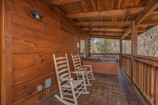 Porch with rocking chairs and hot tub at Smoky Bears Creek, a 2 bedroom cabin rental located in Pigeon Forge