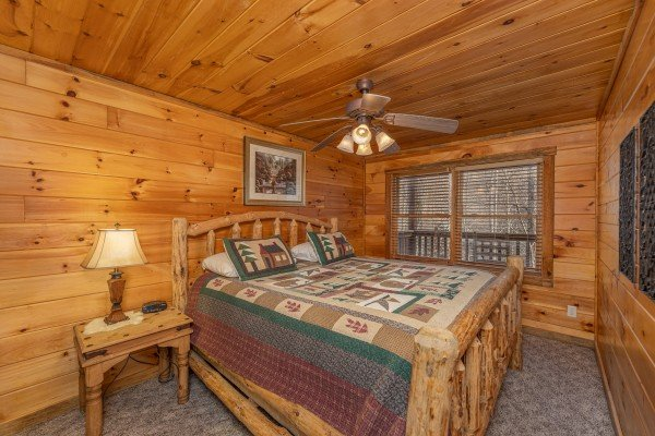 Bedroom with a log bed, table, and lamp at Smoky Bears Creek, a 2 bedroom cabin rental located in Pigeon Forge